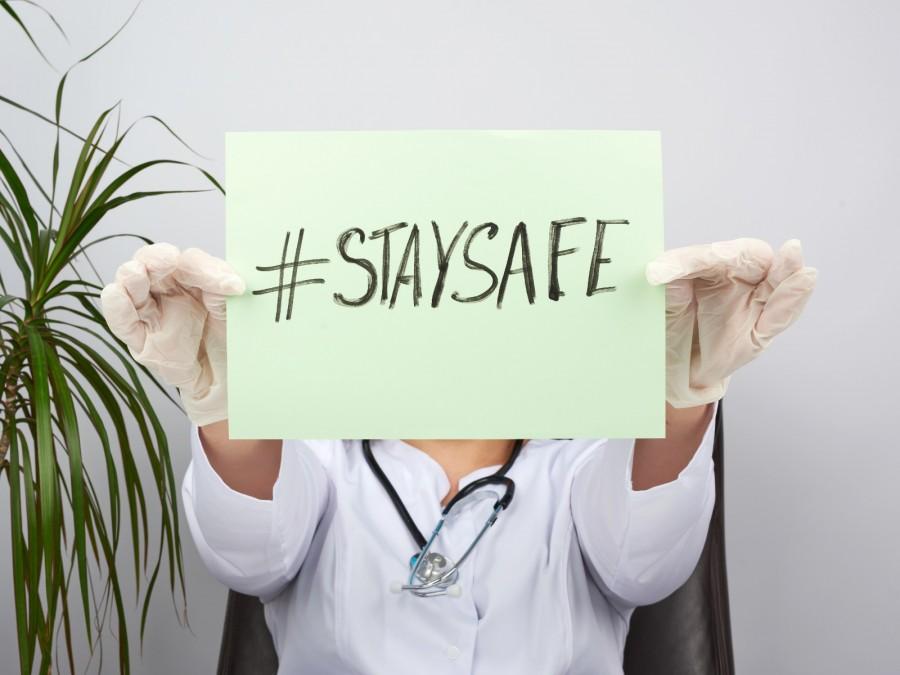 Ärztin mit Handschuhen auf einem Lederstuhl sitzend hält ein Papier vorm Gesicht mit der Aufschrift STAYSAFE (Bleib sicher). Links von ihr eine Palme. Das Bild steht für Vorsicht, Gesundheitsvorsorge, Appell, Aufruf, Ärzterat, Mahnung, Corona, Virus, Pandemie, Verantwortung - Canva