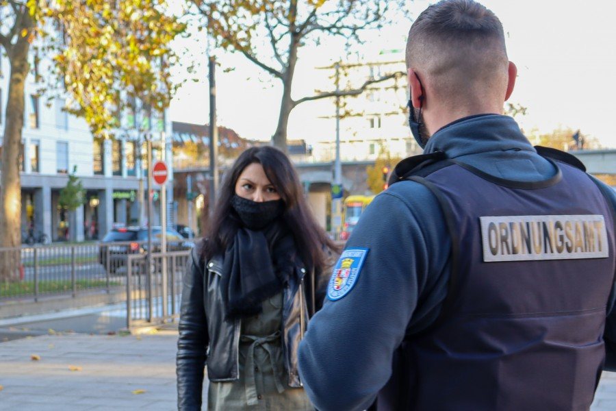 Das Mülheimer Ordnungsamt läuft mit Unterstützung der Polizei Streife im Mülheimer Stadtgebiet, um die Einhaltung der Coronaschutz-Maßnahmen zu kontrollieren. Auf dem Foto befindet ein Mitarbeiter des Ordnungsamtes im Gespräch mit einer Passantin, die eine Alltagsmaske trägt. - Sarah Sternol