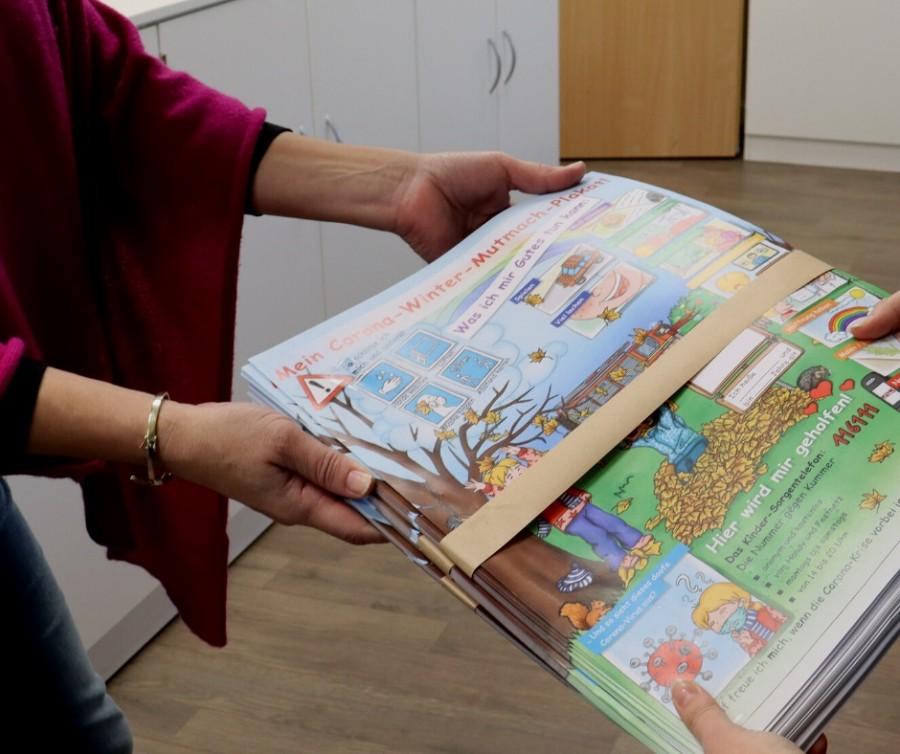 Auf dem Fotos werden die Corona-Winter-Mutmach-Plakate an eine Schulleiterin übergeben. Sie werden an den Grundschulen und Kitas verteilt. Es sind nur die Hände und die Plakate zu sehen. - Jasmin Kramer