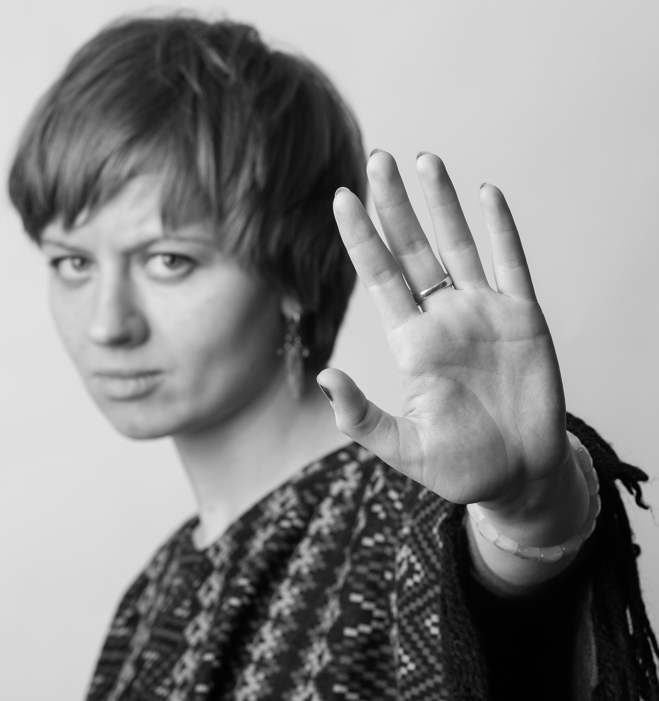 Das Foto Domestic violence - woman put the palm in front of herself von Slava Rutkovski zeigt eine Frau, die selbstbewusst und abwehrend mit der Hand Stop, bis hierher und nicht weiter! signalisiert.