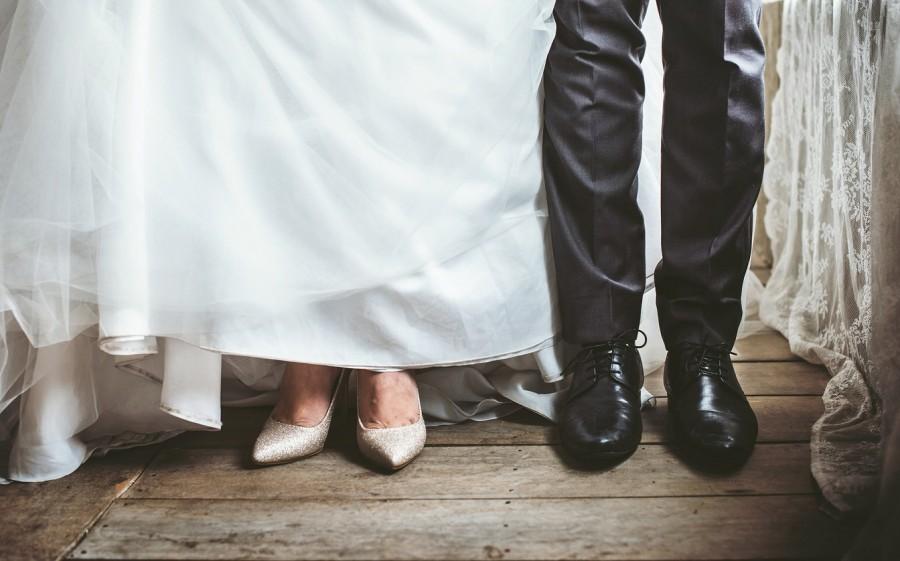 Das Foto zeigt ein Brautpaar in Hochzeitsgarderobe, jedoch ist deren Gesicht nicht erkennbar. Es wird nur der untere Teil des Brautkleides, des Hochzeitsanzuges sowie der Schuhe gezeigt - Pixabay