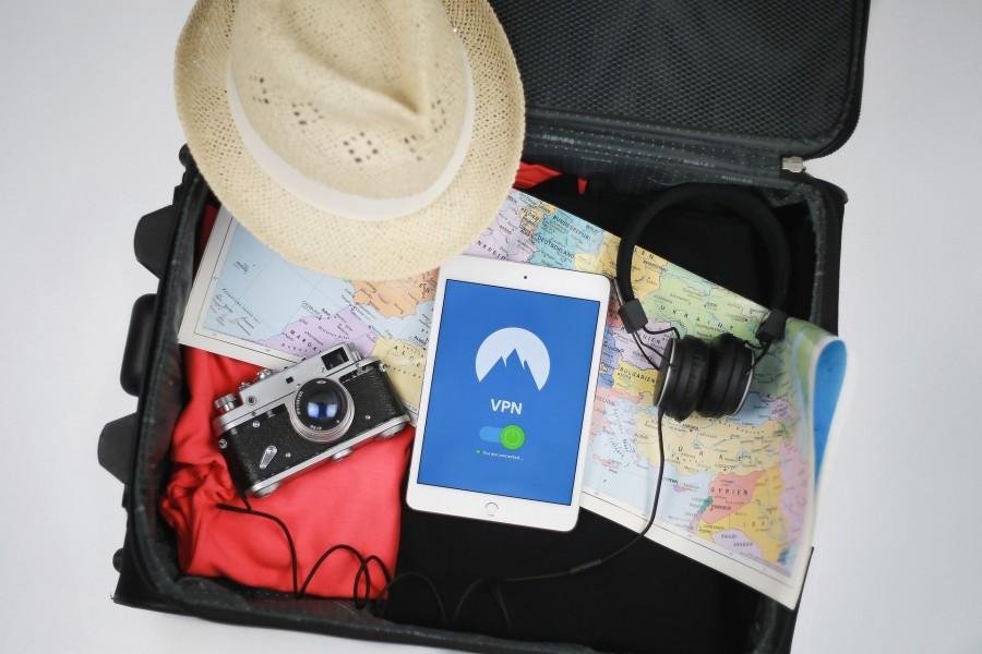 Das Foto zeigt einen offenen Koffer mit einer Weltkarte, einem Fotoapparat, einem Hut, einem Handy und einer roten Jacke - Stefan Coders auf Pixabay