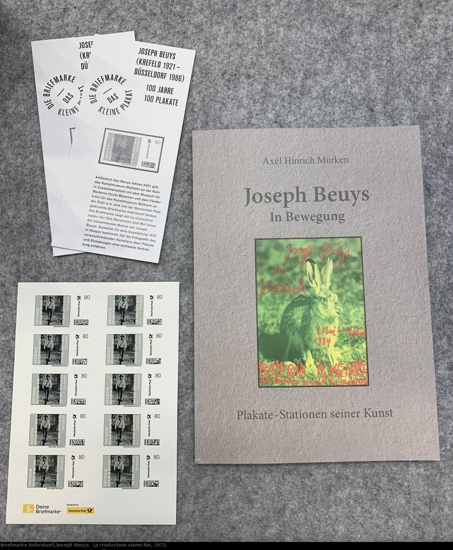 Auf dem Foto ist die neu erschiene Publikation Joseph Beuys: In Bewegung. Plakate Stationen seiner Kunst von Axel Hinrich Murken zu sehen. Außerdem die Briefmarke Individuell anlässlich des 100. Geburtstages von Joseph Beuys. - Briefmarke Individuell,Joseph Beuys: La rivoluzione siamo Noi, 1972 und Joseph Beuys: In Bewegung. Plakate Stationen seiner Kunst von Axel Hinrich Murken Kunstmuseum Mülheim an der Ruhr, Joseph Beuys Estate / VG Bild-Kunst Bonn, 2021