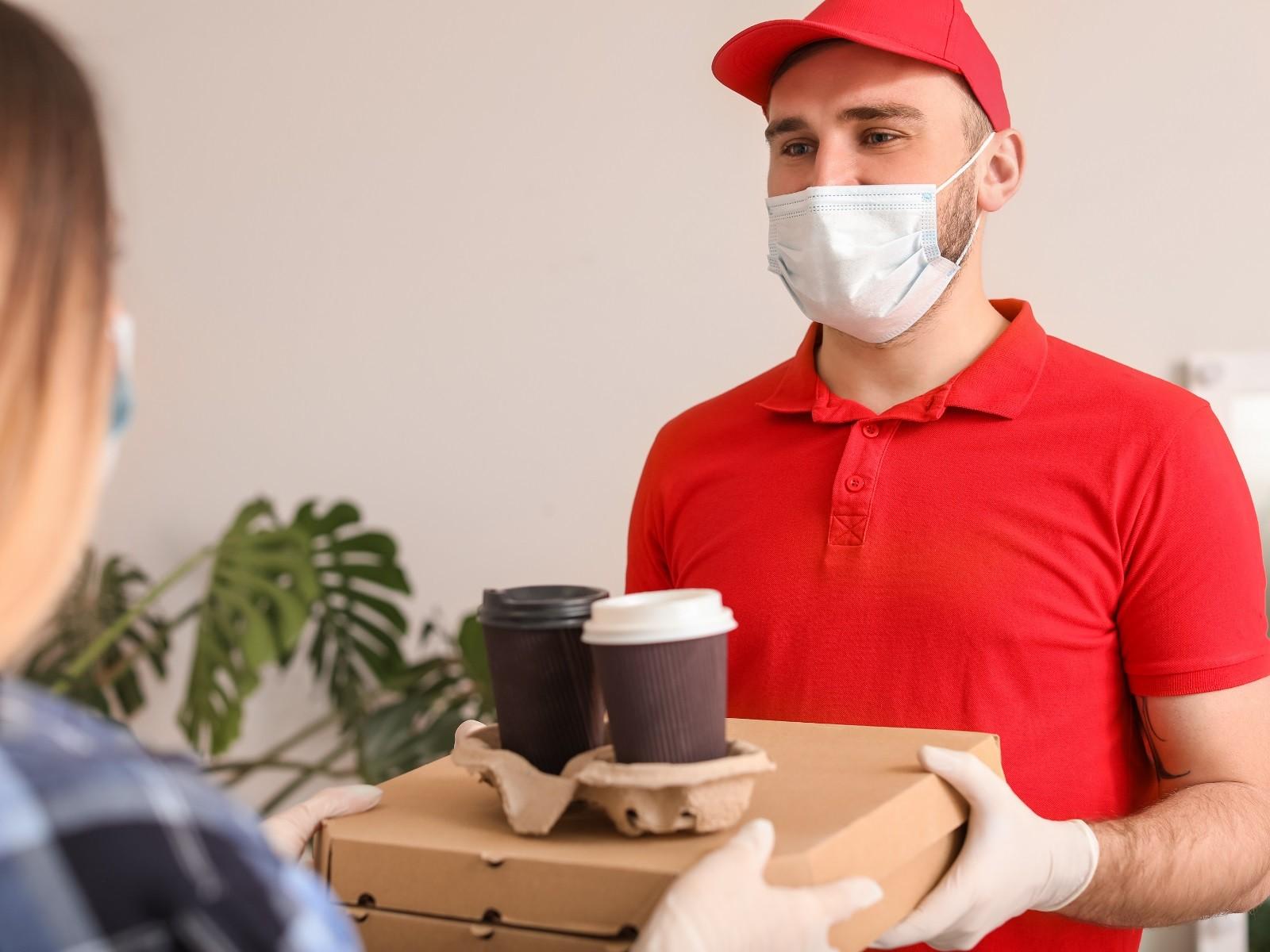 Das Foto zeigt einen Mann in rotem T-Shirt mit roter Kappe auf, der eine Maske und Handschuhe trägt, und Nahrung und Getränke an eine Frau liefert. Quelle/Autor: Canva