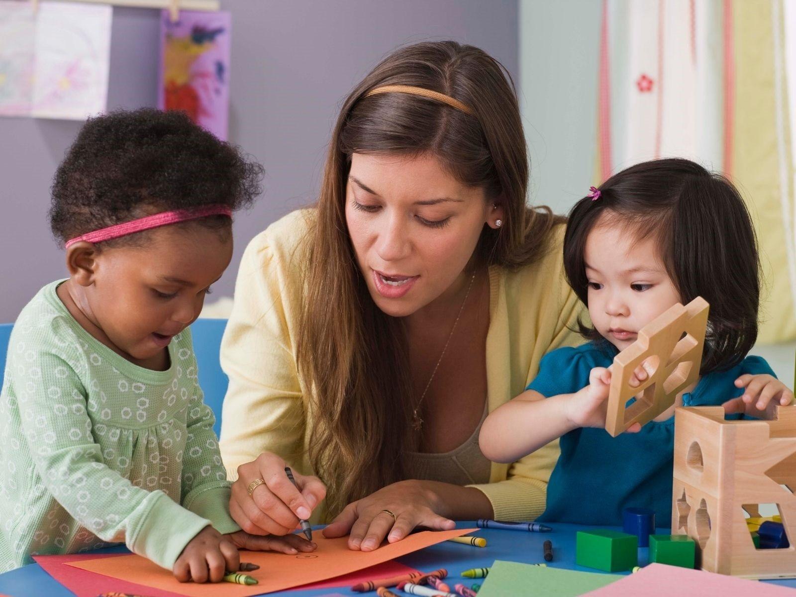 Kindertagespflegeperson spielt mit zwei kleinen Kinder. Quelle/Autor: Canva