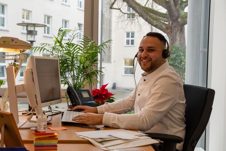 Valentino, 24 Jahre, Azubi zur Servicefachkraft für Dialogmarketing. Er arbeitet im KommunikationsCenter und ist ein Gesicht der Stadt in der Facebook-Kampagne StadtzeigtGesicht. Das Foto zeigt Valentino an seinem Arbeitsplatz. - Tobias Grimm