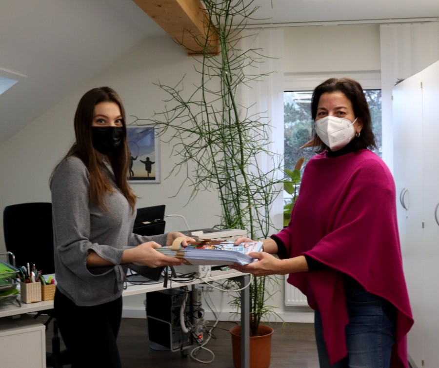 Auf den Foto übergibt Benja Tinla die Corona-Winter-Mutmach-Plakate an die Schulleiterin der Gemeinschaftsgrundschule am Saarnberg, Uta Lang, die Mutmach-Plakate. Benja Tinla verteilt die Plakate ehrenamtlich. - Jasmin Kramer