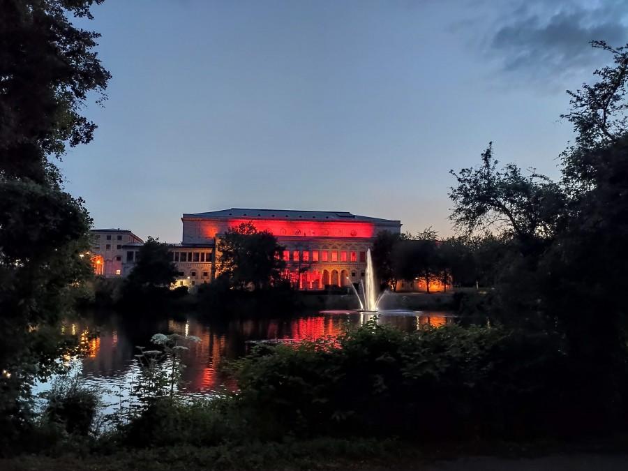 Night of light 2020. In Mülheim und Bundeweit wurden Gebäude mit rotem Licht illuminiert, um auf die dramatische Situation in der Veranstaltungswirtschaft, ausgelöst durch die Corona-Krise, aufmerksam zu machen. Das Foto zeigt den Blick auf die rot beleuchtete Stadthalle von der Ruhrpromenade aus. Davor die ebenfalls erleuchtete Wasserfontäne am Stadthallengarten auf der Ruhr. Im Vordergrund grüne Büsche. - Anna Moczurad/MST